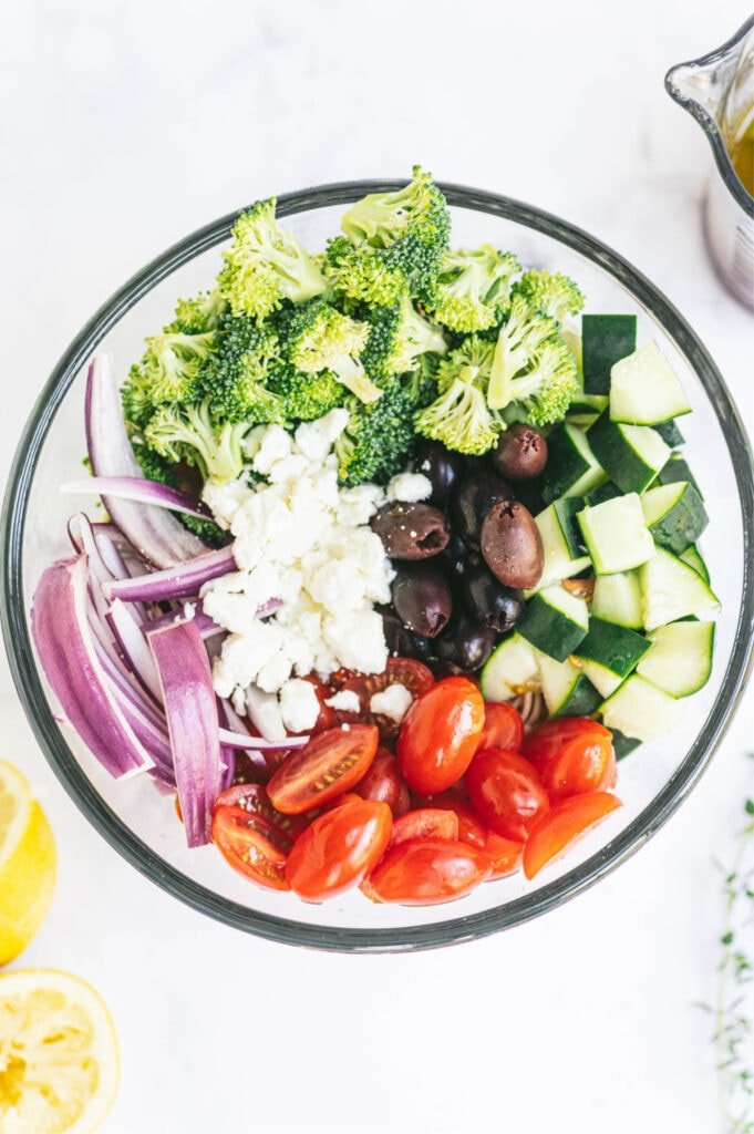 Sliced red onions, crumbled feta cheese, kalamata olives, halved grape tomatoes, diced cucumbers, and chopped broccoli in a glass bowl.