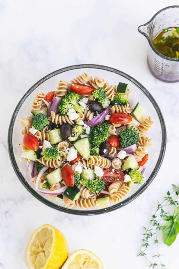 A large bowl of pasta veggie salad with dressing on the side.