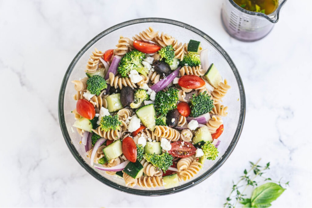 A large bowl of pasta salad with tomatoes, cucumbers, broccoli, red onions, feta cheese, olives, and pasta. There is dressing in a small pitcher off to the side.