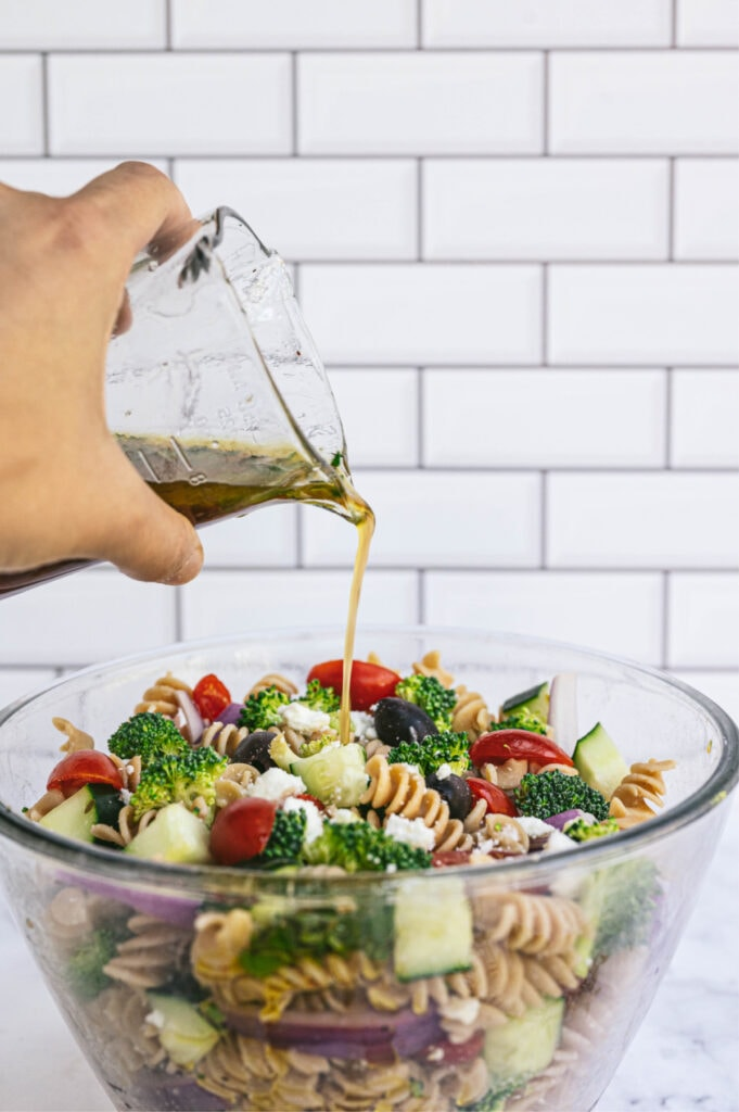 A hand pouring dressing from a glass container into a bowl bowl of Greek pasta salad with white subway tiles in the background.