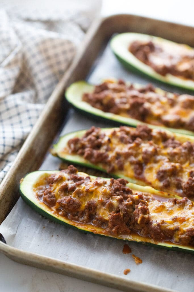 Parchment lined baking sheet with four zucchini taco boats topped with ground beef and cheese.