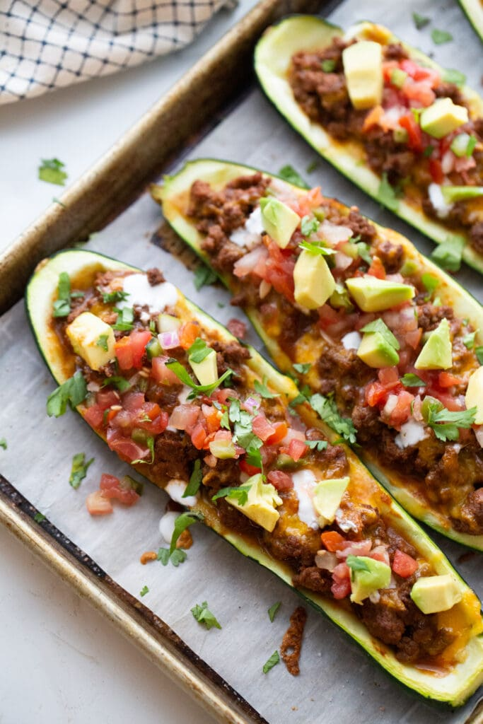 Stuffed zucchini on a parchment lined baking sheet topped with taco meat, cheese, pico, avocado, and cilantro.