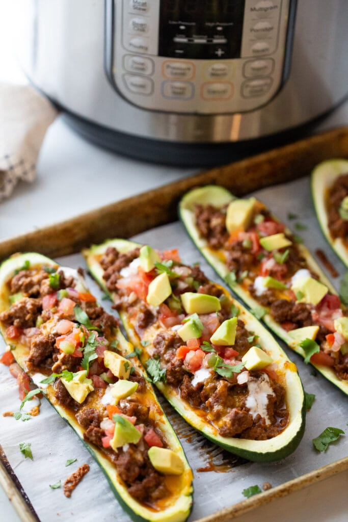 High angle photo of zucchini boats ground beef, pico, and avocado on a baking sheet. There is an instant in the background to cook the taco meat.