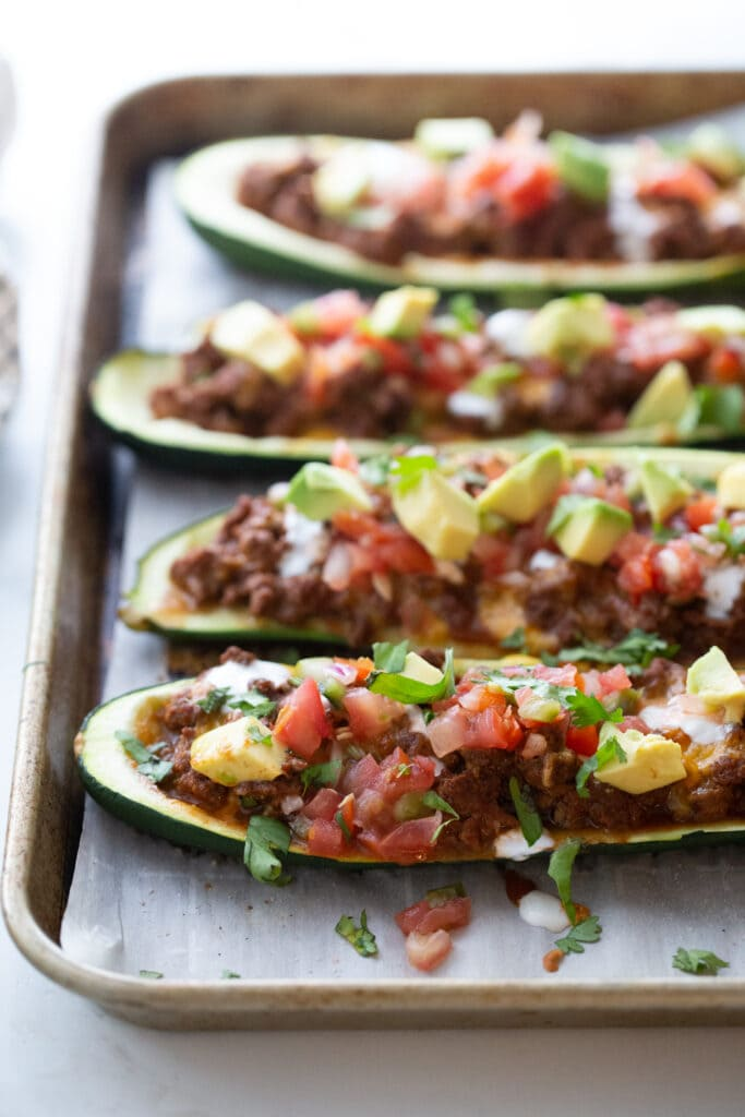 Four zucchini boats with ground beef, taco seasoning, cheese, pico de gallo, and avocado on a parchment lined baking sheet.