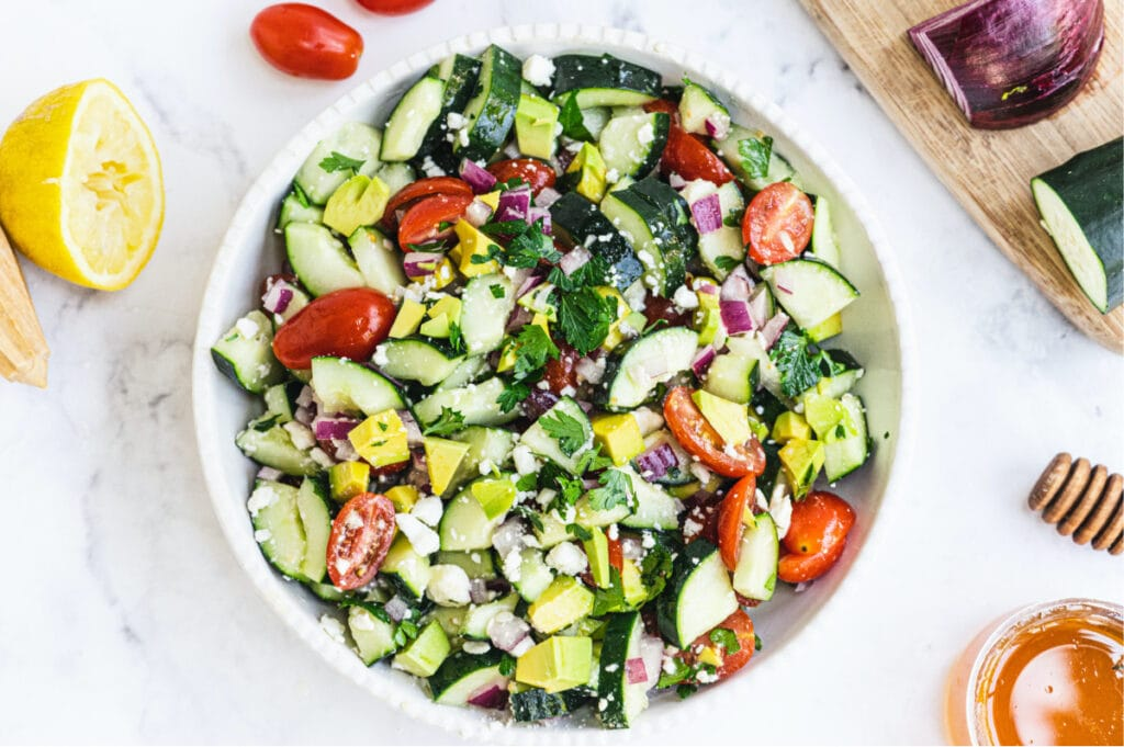 A large white bowl of summer cucumber tomato salad topped with avocado and feta cheese with other ingredients on the side of the bowl.