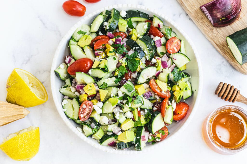 Salad made of tomatoes, cucumbers, red onion, feta, and avocado in a large white serving bowl. Lemons, honey, tomatoes, red onion, and cucumber all surround the photo at the edges.