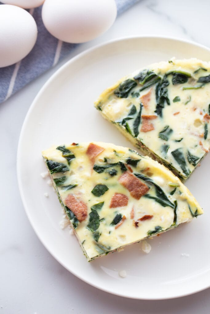 overhead closeup: two slices of bacon cheese egg frittata on white plate