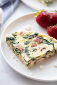 slice of Instant Pot frittata on white plate with fresh strawberries