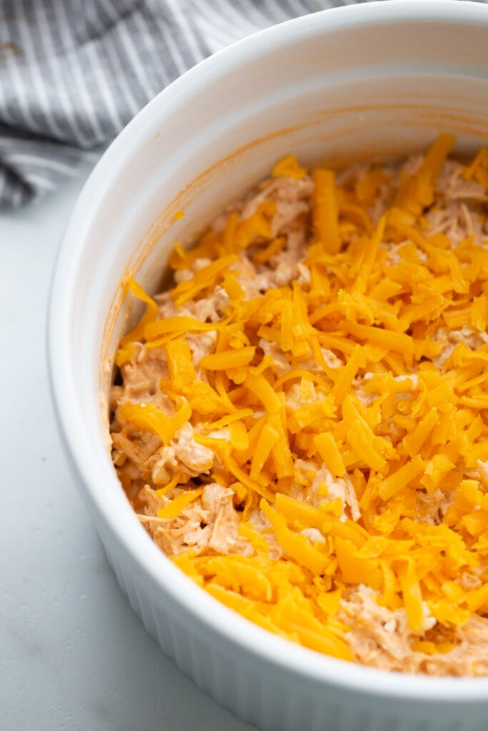 White casserole dish with buffalo chicken dip and topped with shredded cheddar cheese, ready for the oven.
