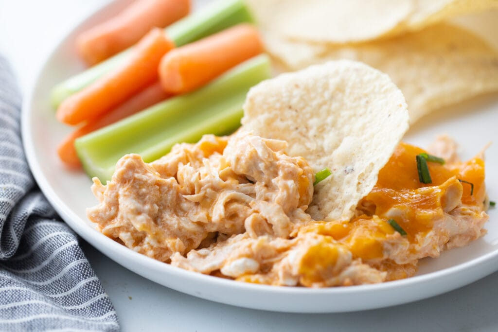 White rimmed plate with buffalo chicken dip recipe and a chip sticking out of the top. Baby carrots, celery, and tortilla chips are in the background of the plate.