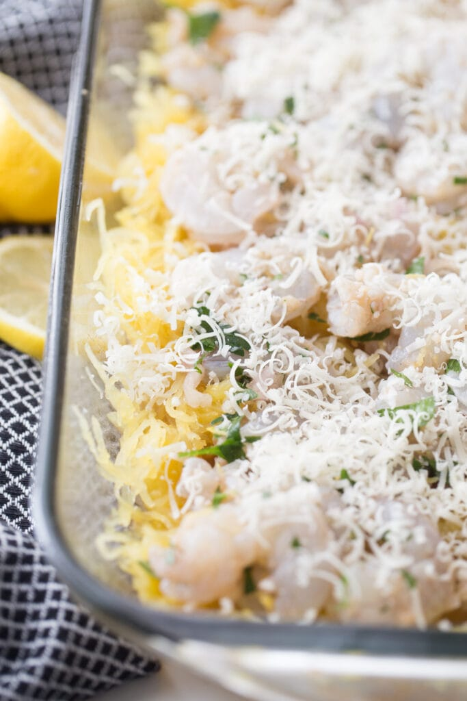 freshly grated parmesan cheese on top of a spaghetti squash casserole, ready for baking