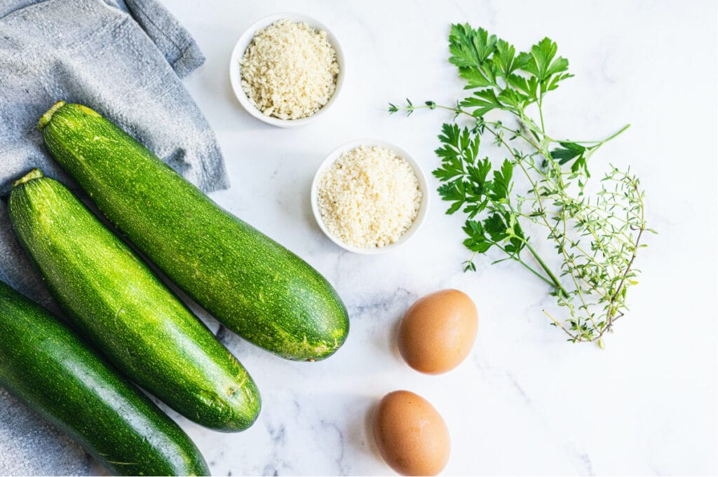 Overhead image: ingredients to make zucchini fritters- whole zucchinis, bread crumbs, Parmesan cheese, eggs, and herbs.