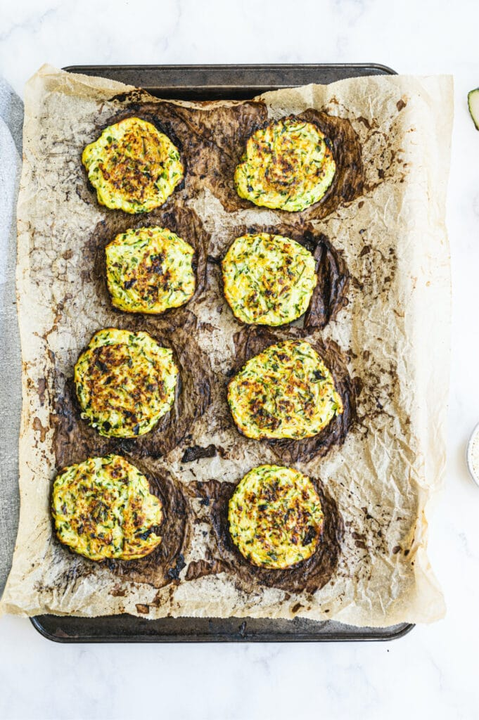 Overhead image: Baked zucchini fritters on a parchment lined sheet pan