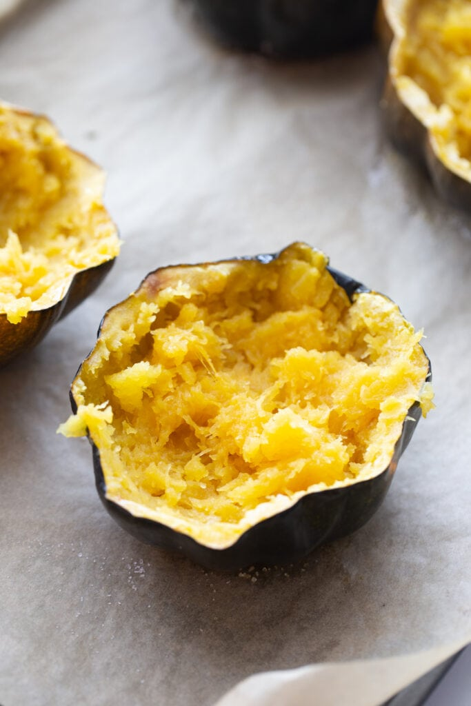 Mashed acorn squash halves, after being roasted in the oven, and ready to be stuffed on a parchment lined baking sheet.