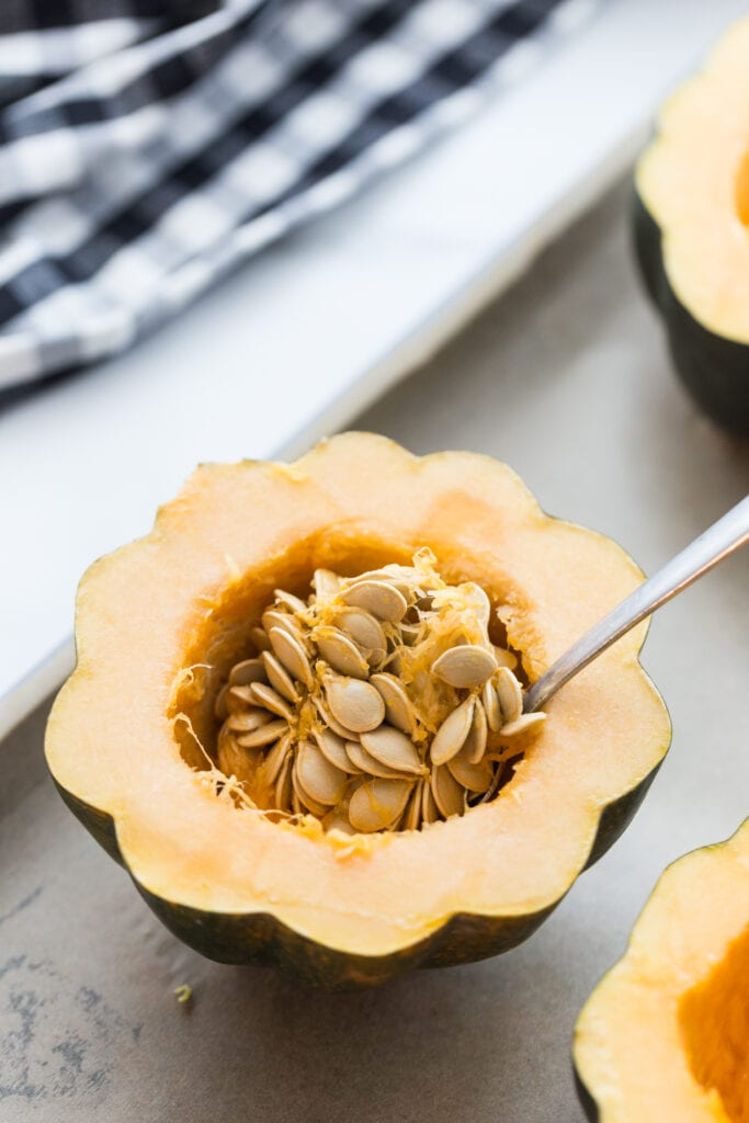 Acorn squash cut in half with a spoon ready to scoop out the seeds of the squash before roasting it in the oven.