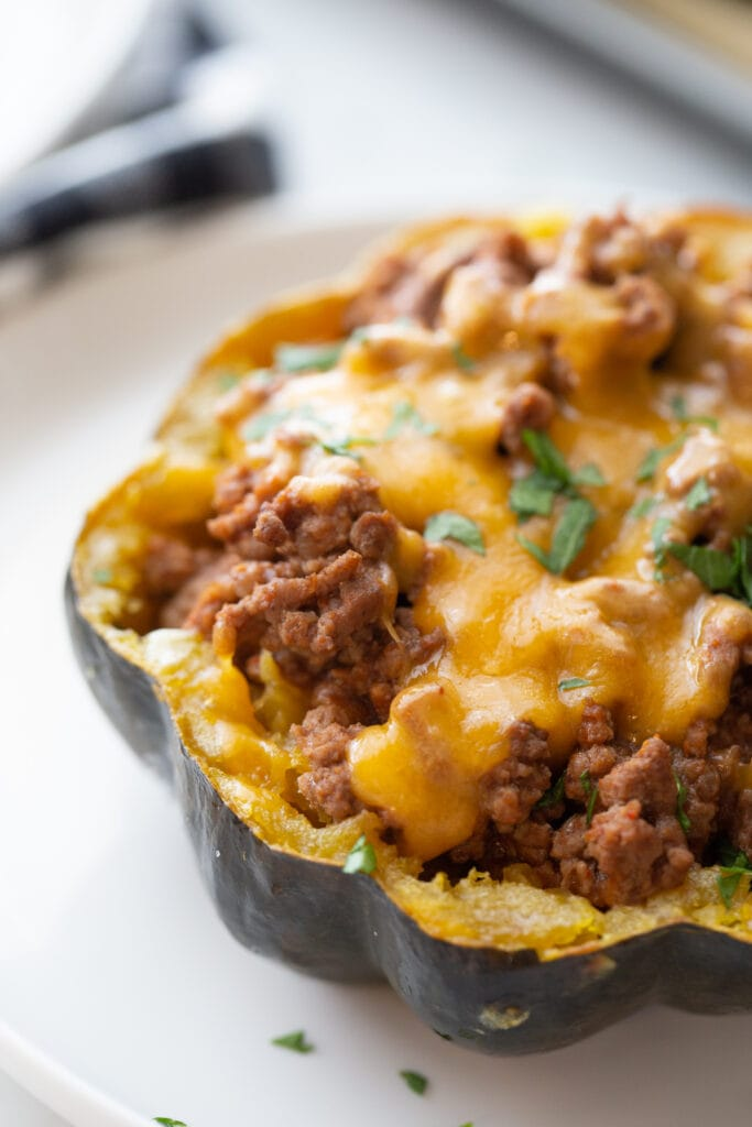 Taco stuffed acorn squash topped with cheese and cilantro on a white plate.