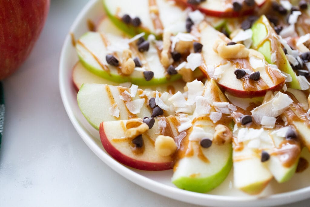 Close up photo of a plate of apple nachos- sliced red and green apples topped with shredded coconut, mini chocolate chips, walnuts, and caramel sauce.
