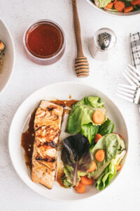 honey glazed salmon oven baked on a white plate with side salad