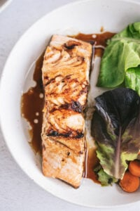 overhead closeup: salmon filet with teriyaki glaze on white plate with garden salad