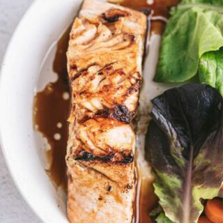 overhead closeup: salmon filet with teriyaki glaze on white plate with garden salad
