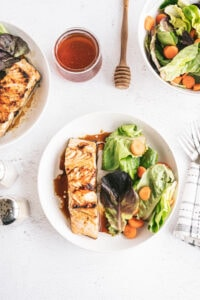 overhead photo of plated grilled salmon dinner on white background with salad, jar of honey and dipping wand