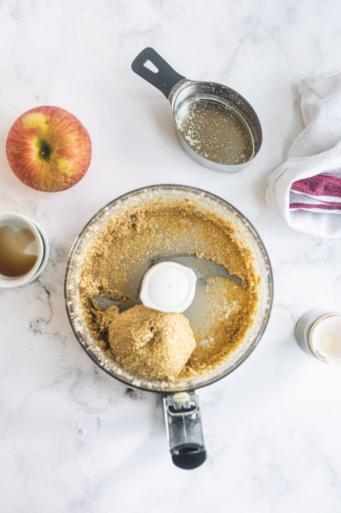 Overhead photo of a food processor with a ball of dough made primarily from almond flour and oat flour