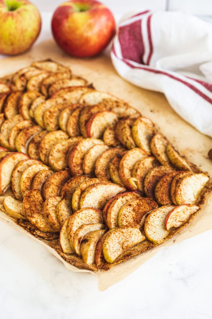 Baking sheet with sliced apples topped with cinnamon on a Gluten Free crust
