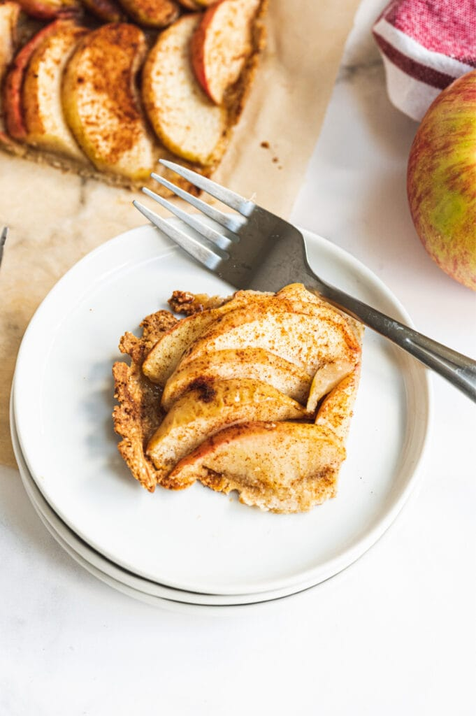 A piece of gluten free apple tart on a white plate with a fork on the side.