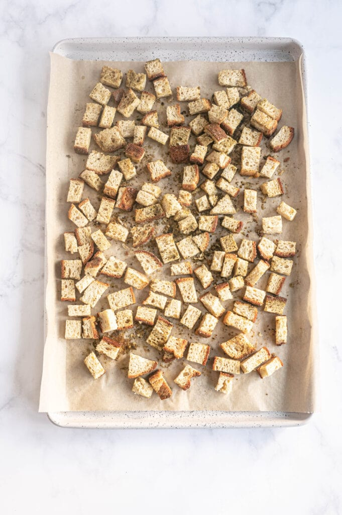 Bread cubes on a parchment lined baking sheet, ready to be toasted in the oven.