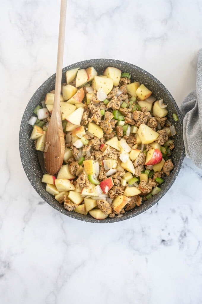 Overhead photo of poultry sausage, veggies, and apples in a skillet, with a wooden spoon resting on the side.