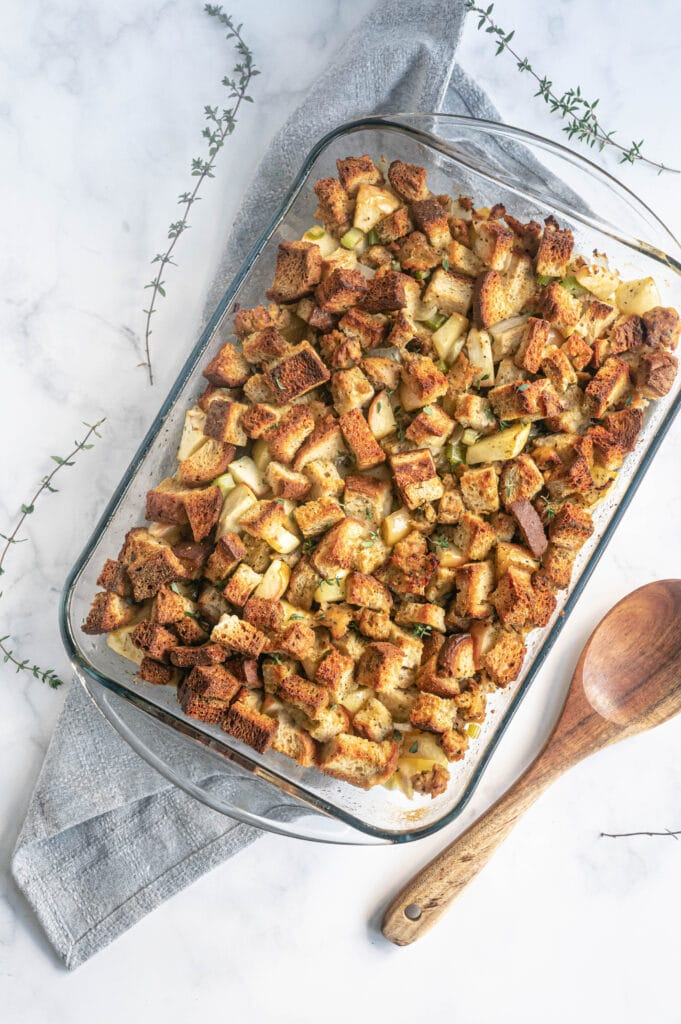 Glass baking dish filled with homemade bread stuffing with a wooden spoon on the side.