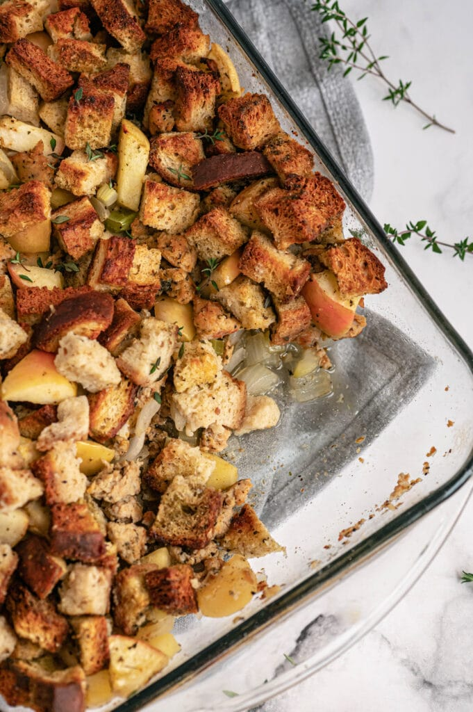 Overhead photo of a glass baking dish of stuffing with a portion missing from the corner.