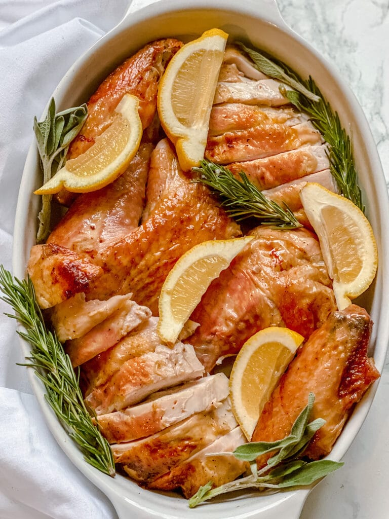Carved turkey pieces (with the skin on) in a serving dish with lemon wedges, and sprigs of rosemary and sage.