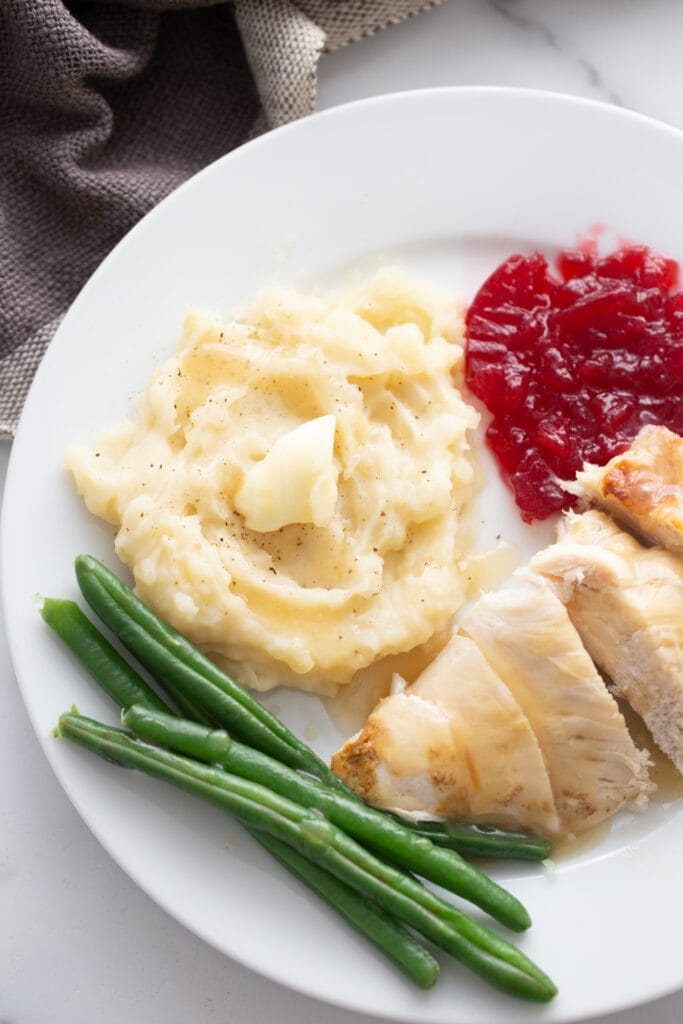 Sliced turkey breast with gravy, mashed potatoes with butter, green beans, and cranberry sauce on a white plate.
