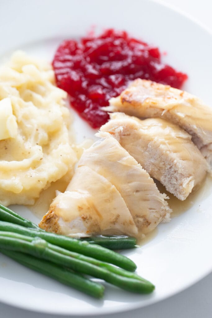 Close up photo of Instant Pot turkey breast topped with gravy on a plate with green beans, cranberry sauce, and mashed potatoes