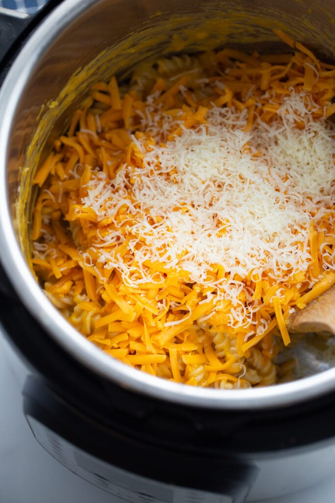 Overhead photo of shredded cheese, cooked pasta, and butternut squash ready to be mixed in the instant pot