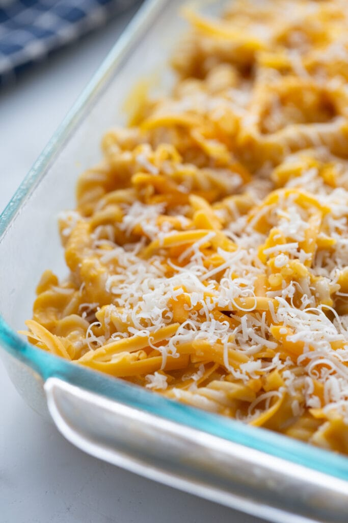 Glass baking dish of butternut squash mac and cheese topped with shredded cheese, ready for the oven.