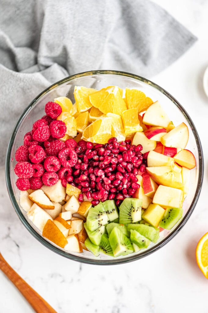 Several diced fruits are placed in a glass bowl on a white marble surface.