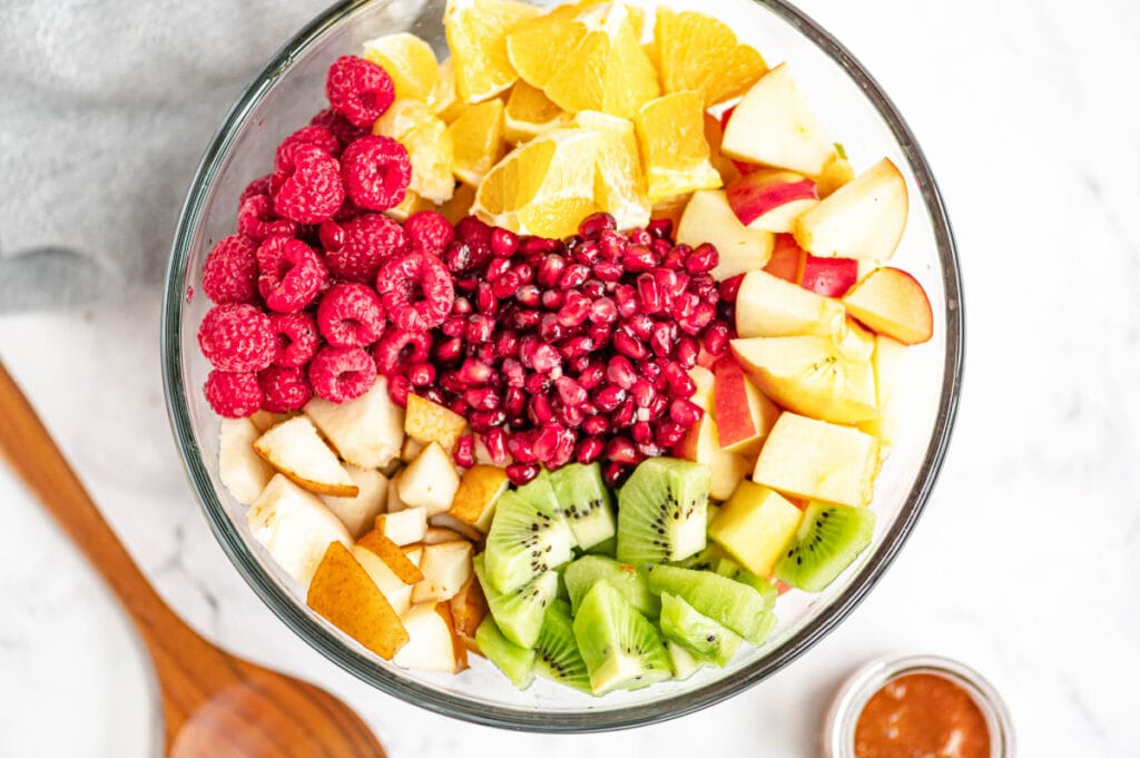 Multiple diced fruits are placed perfectly in a large glass bowl on a white marble surface.