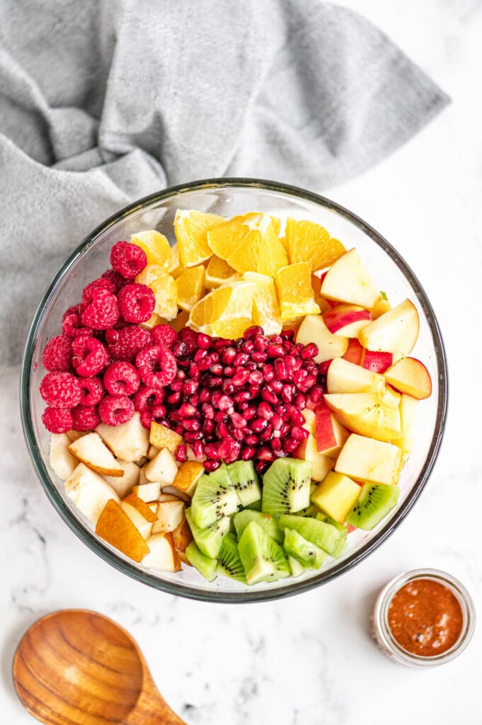 Fruits are diced and placed evenly in a large glass bowl on a white marble surface, near a wooden spoon and gray towel.