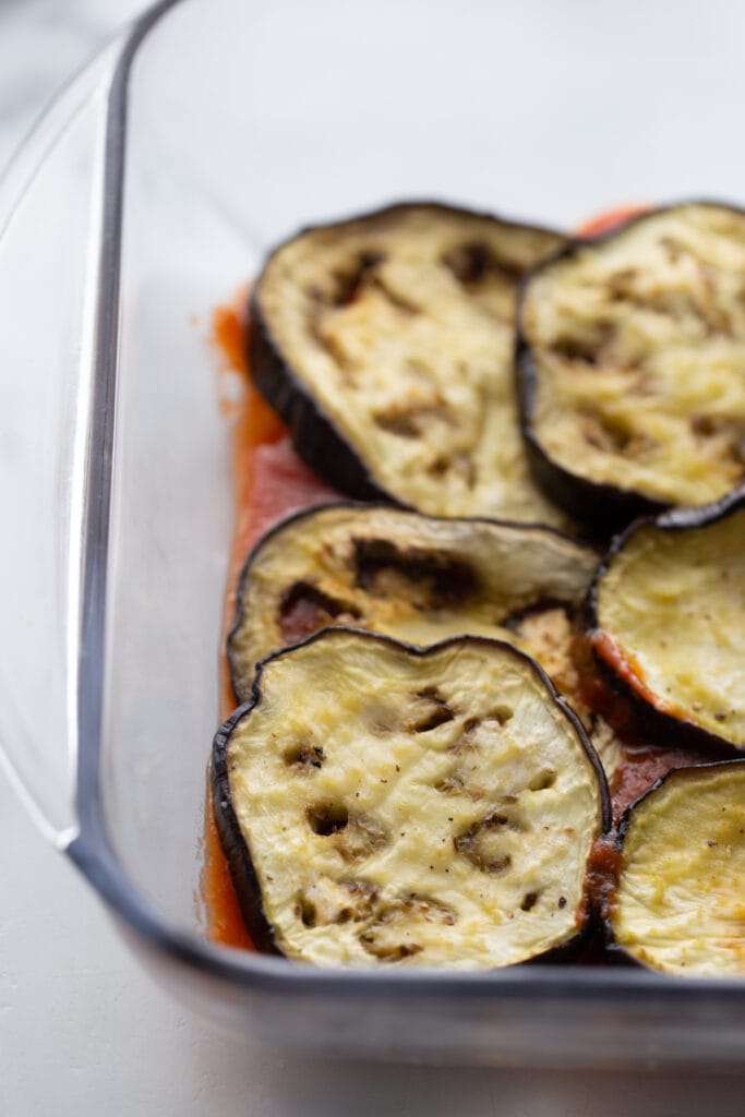 Eggplant slices are placed on top of tomato sauce in a glass baking dish.
