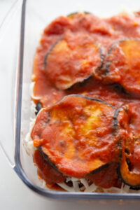 Tomato sauce covers several layers of eggplant slices.