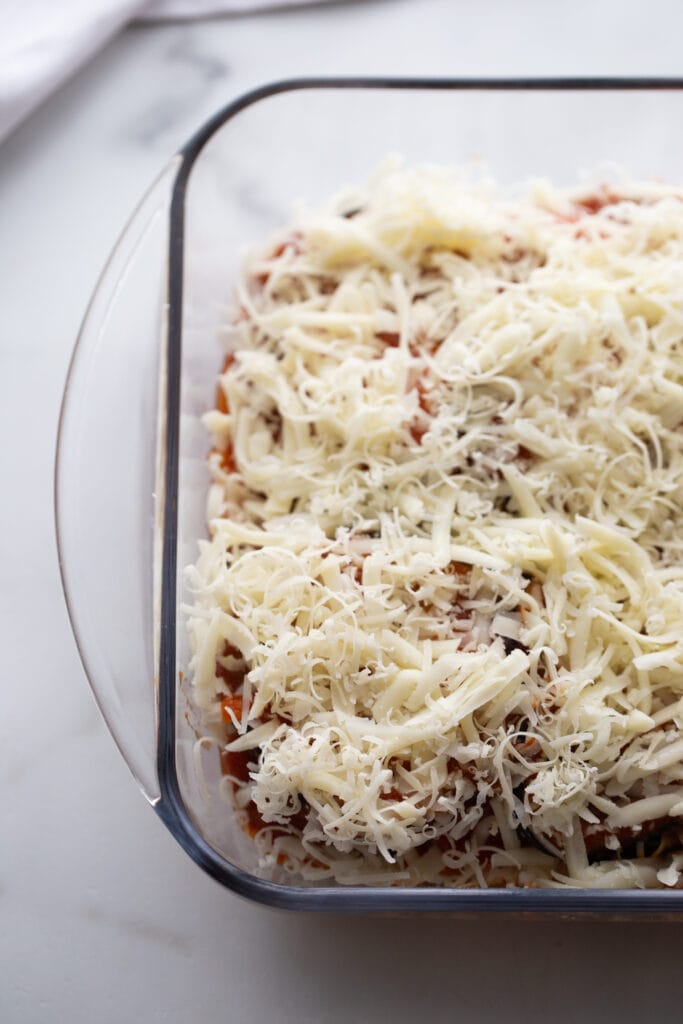 Parmesan and mozzarella cheese cover an uncooked eggplant dish.