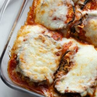 A glass baking dish holds freshly baked slices of eggplant parm.