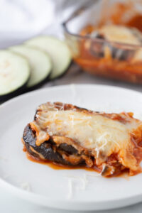 A portion of eggplant parm is placed on a white plate, ready to be eaten.