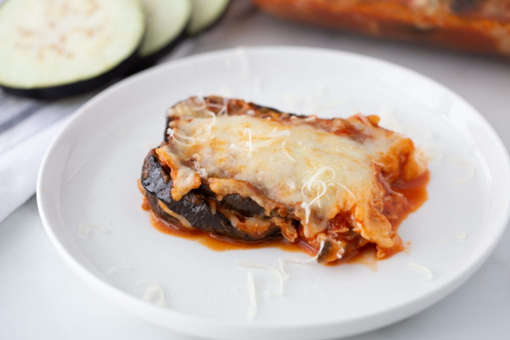 A serving of cheesy eggplant parm is presented on a white plate.