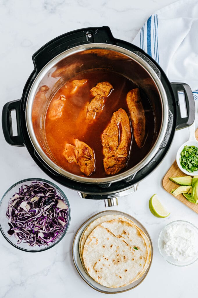 Fresh ingredients like purple cabbage and limes surround an Instant Pot containing cooked chicken.