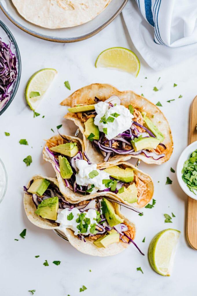 Three chicken tacos are garnished with cilantro and greek yogurt.