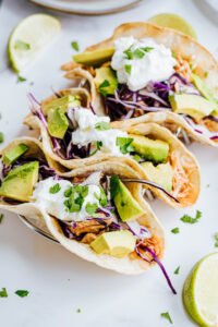 A close up shot reveals multiple fresh veggies garnishing three chicken tacos.
