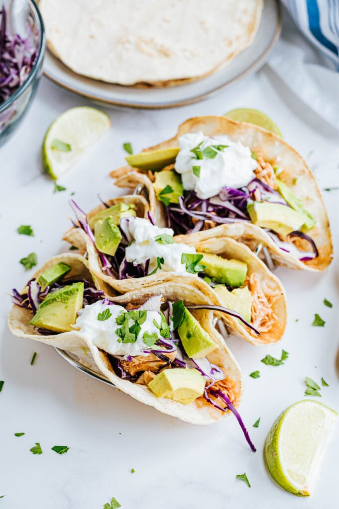 Three chicken tacos are placed on a white surface.